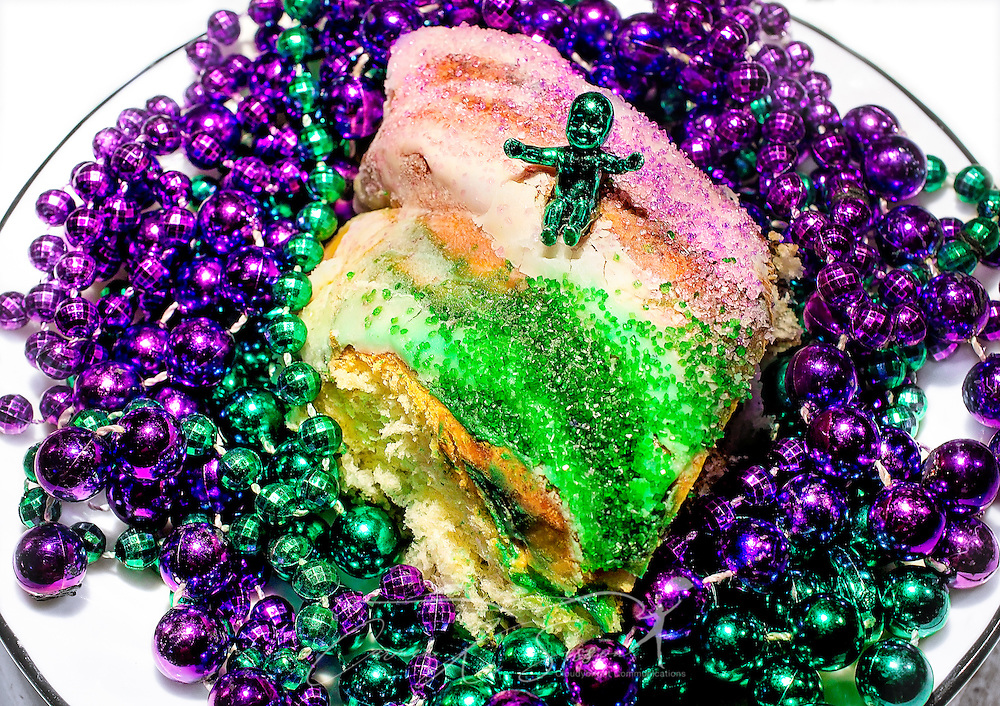 A Mardi Gras King Cake with a plastic baby is pictured with purple and green Mardi Gras beads, March 12, 2014, in Mobile, Alabama. The king cake is traditionally made of fried or baked dough, topped with green, purple, and gold icing or sugar. Modern king cakes sometimes contain fillings such as raspberry, strawberry, cream cheese, or cinnamon. The king cake represents the three kings who visited the Christ child on Epiphany, and the cake usually includes a small plastic baby inside to represent the Christ child. French settlers held the first Mardi Gras in Mobile, Alabama in 1703. Mardi Gras is a season of revelry that extends from Epiphany, 12 days after Christmas, to Fat Tuesday, the day before Ash Wednesday and the beginning of Lent. (Photo by Carmen K. Sisson/Cloudybright).