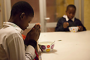 A boy prays before he takes his breakfast at the Woodstock shelter. - Images from the Project South Africa: Working With Nonprofits workshop held in Cape Town, South Africa. Image © Steve Moakley/Momenta Workshops 2013.