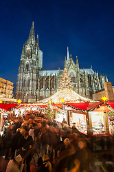 Night view of Christmas Market in Cologne with cathedral to rear, Germany