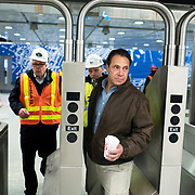 December 12, 2016 - New York, NY :  New York State Governor Andrew M. Cuomo, in brown jacket at right, passes through a turnstyle as he enters the 96th Street Second Avenue subway station on Monday morning. After years of delays, the new second avenue subway line is nearing completion. The governor visited the soon-to-open second avenue subway project on Monday morning with this photographer and New York Times reporter Emma G. Fitzsimmons.  CREDIT: Karsten Moran for The New York Times