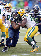 Green Bay Packers running back Eddie Lacy (27) gets stuffed on a run by Seattle Seahawks defensive end Michael Bennett (72) for a loss of 3 yards with less than five minutes left in the fourth quarter during the NFL week 20 NFC Championship football game against the Seattle Seahawks on Sunday, Jan. 18, 2015 in Seattle. The Seahawks won the game 28-22 in overtime. ©Paul Anthony Spinelli
