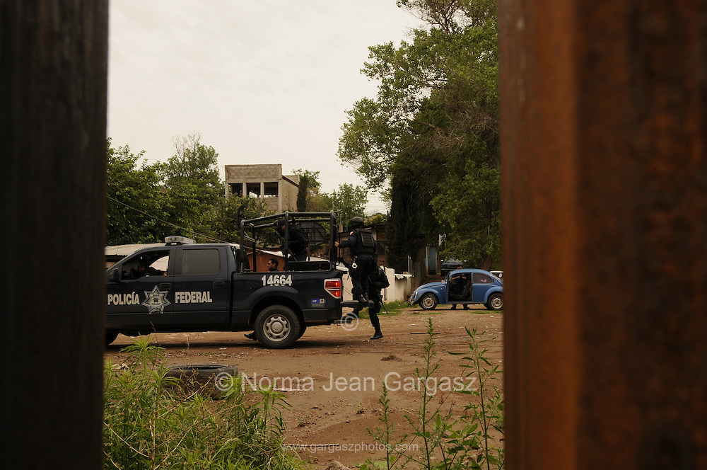 Seen through the border wall in Nogales, Arizona, USA, heavily armed federal police in Nogales, Sonora, Mexico, patrol Colonia Buenos Aries, a residential area also known for smuggling and criminal activities.