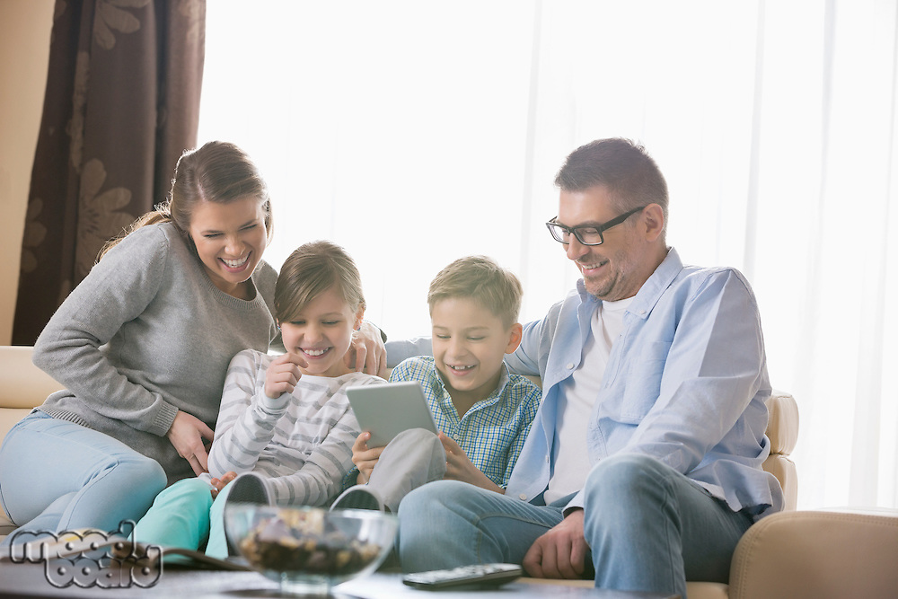 Cheerful family using tablet PC together in living room