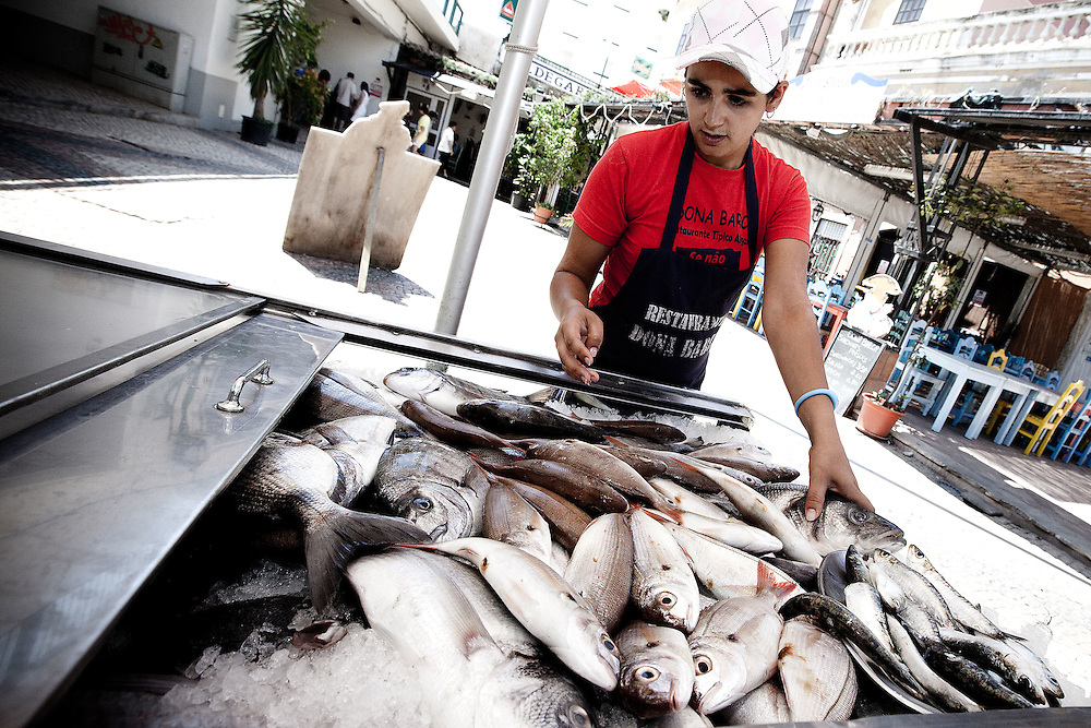A vendor selling fresh fish in downtown Portimao. Portimao Portugal Match Cup 2010. World Match Racing Tour. Portimao, Portugal. 24 June 2010. Photo: Gareth Cooke/Subzero Images