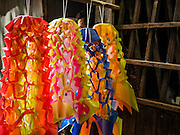 10 SEPTEMBER 2016 - BANGKOK, THAILAND: Traditional Thai paper flowers that are used as decorations around temples and villages hang in front of home during a community party in Pom Mahakan. Forty-four families still live in the Pom Mahakan Fort community. The city of Bangkok has given them provisional permission to stay, but city officials say the permission could be rescinded and the city go ahead with the evictions. The residents of the historic fort have barricaded most of the gates into the fort and are joined every day by community activists from around Bangkok who support their efforts to stay.                PHOTO BY JACK KURTZ