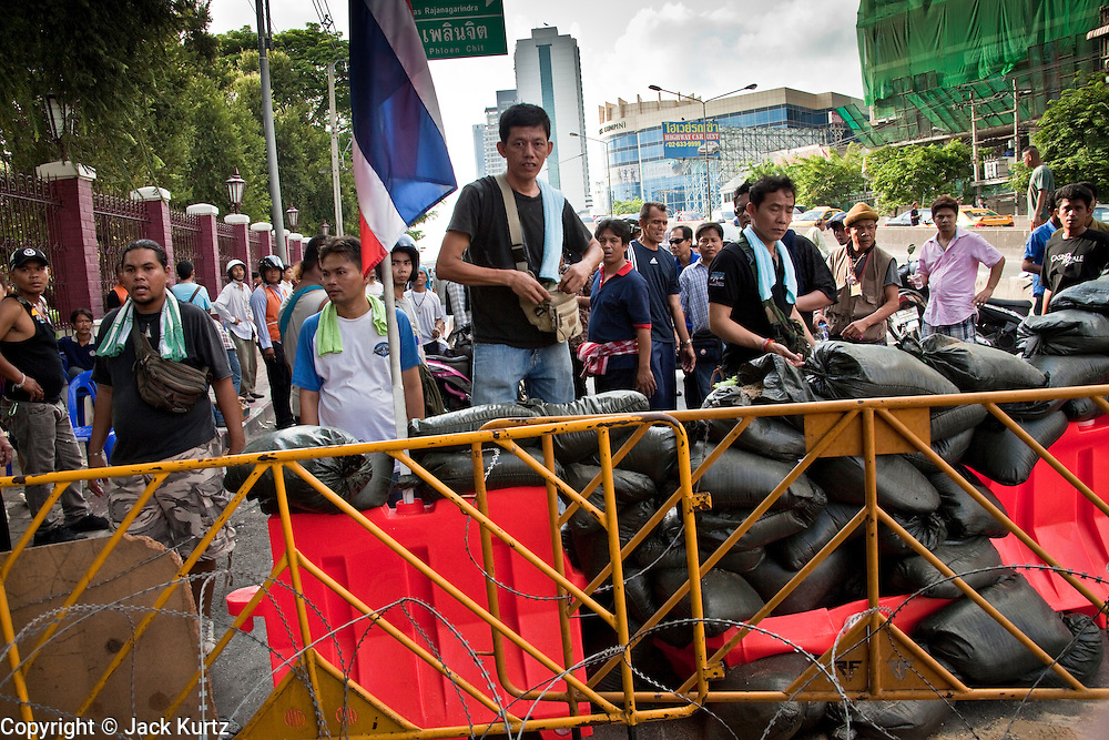 14 MAY 2010 - BANGKOK, THAILAND: Red Shirt protesters at the barricade they captured from soldiers at the intersection of Rama IV and Witthayu Roads in Bangkok Friday morning. Tensions among Red Shirt protesters demanding the dissolution of the current Thai government rose overnight after Seh Daeng, the Red Shirt's unofficial military leader was shot in the head by a sniper. Gangs of Red Shirts have taken over military checkpoints on Rama IV and are firing small rockets at military helicopters and army patrols in the area. Troops have responded by firing towards posters.  PHOTO BY JACK KURTZ