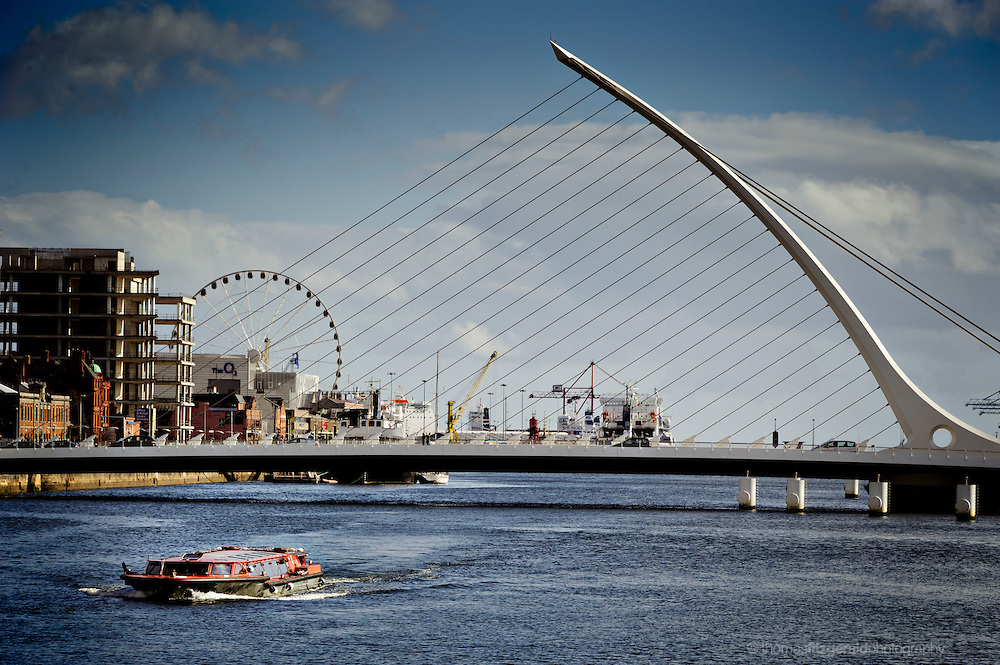 A River Boat passes under the bridge of Dublin Harbour, with the Dublin Eye, and the Port of Dublin in the background