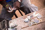A man sands small pieces of cow horn at the Village Artisanal de Ouagadougou, a cooperative that employs dozens of artisans who work in different mediums, in Ouagadougou, Burkina Faso, on Monday November 3, 2008.