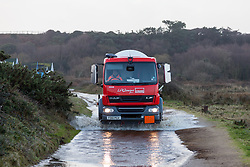 © Licensed to London News Pictures. 06/01/2014. Mudeford Spit, Christchurch, Dorset, UK. A lorry passing through flood water as it is delivering LPG next to the beach huts on Mudeford Spit near Christchurch in Dorset, UK. The beach huts sell for an average of around £140,000. Dorset is expected to be one of the worst affect areas, with more heavy rain and flooding forecast. Photo credit : Rob Arnold/LNP