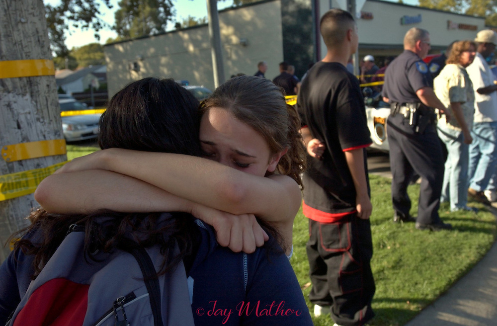 A witness (facing the camera) to the shooting of a fellow McClatchy High School student is consoled by a friend before Sacramento police officers take her away from the scene of the incident at 5th and Freeport Blvd.  Tuesday, September 30, 2003.