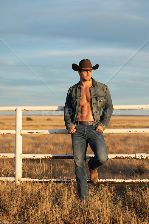 hot cowboy without a shirt in a denim jacket at sunset