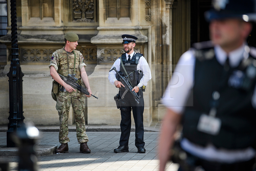 © Licensed to London News Pictures. 25/05/2017. London, UK. An armed soldier and armed police officer stand on guard at the Houses of Parliament in Westminster, following a terrorist attack in Manchester, northern England, earlier this week. 23 people were killed an dozens more injured when Salman Abedi set off a suicide bomb at an Ariana Grande concert.  Photo credit: Ben Cawthra/LNP