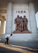 Kid roller skating in front of the Monument To The Victorious Fatherland Liberation War, in Pyongyang, North Korea.