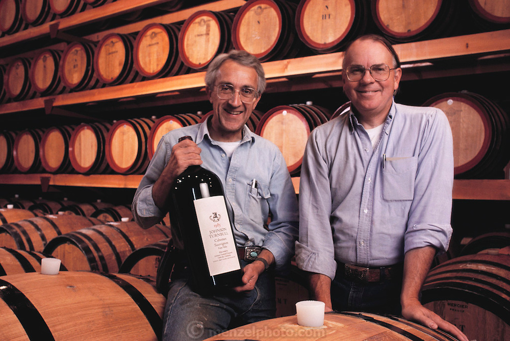 Johnson Turnbull Winery co-founders, Reverdy Johnson (attorney, at left) and Bill Turnbull (architect), in the barrel cellar of the winery. Mr. Johnson is holding a 6-liter bottle of Cabernet Sauvignon; their best known wine.  The winery was purchased in 1992 by Patrick O'Dell and renamed Turnbull Winery. Photographed in 1990. Oakville, Napa, Valley, California. MODEL RELEASED.