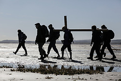© Licensed to London News Pictures. 25/03/2016. Holy Island, UK. Pilgrims walk with a cross as the Good Friday crossing makes its  journey to Holy Island on March 25, 2016 in Lindisfarne in Northumberland, north east England. People, young and old, celebrated Easter by crossing the tidal causeway during the annual Christian pilgrimage. Every year people of all ages, from all over the world and from all realms of Christian life walk together at Easter to Holy Island. Photo credit: Stuart Boulton/LNP