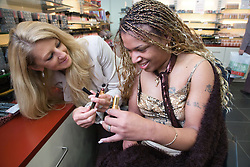 Carer and young woman with Cerebral Palsy shopping choosing lipstick,