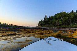 The bow oif a boat leaving Gosling Island atfter sunset in Casco Bay, Harpswell, Maine.