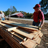 Thomas Wells | BUY AT PHOTOS.DJOURNAL.COM<br /> Bo Stevens, left, and Joe Williamson place another cut board on their stack of lumber.