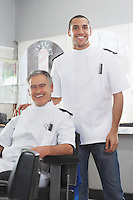Two barbers in barber shop portrait
