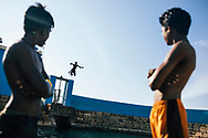 Young boy jumps off the wall into the Keerimalai Springs, sacred pools fed by sea waters on the northern shores of the Jaffna Peninsula, Sri Lanka, Asia