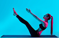 one caucasian woman exercising Navasana  boat pose yoga exercices  in silhouette studio isolated on blue background