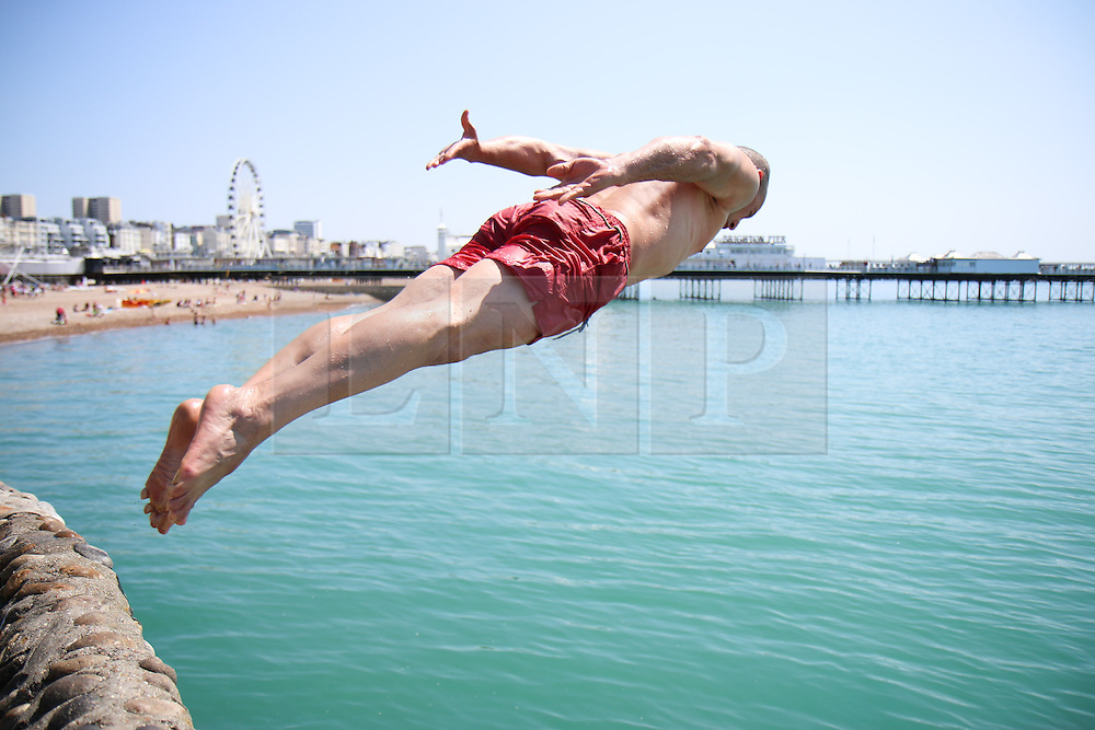 © Licensed to London News Pictures. 03/07/2015. Brighton, UK. A man dives into the sea from the pontoon next to Brighton Pier while hundreds of people relax in the sunshine on Brighton Beach, today July 3rd 2015. Photo credit : Hugo Michiels/LNP