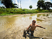14 JULY 2015 - THAILAND:   A laborer walks through the muck back to shore after net fishing in a khlong (irrigation canal) in Pathum Thani province. The canal, which is normally about 10 meters deep, is essentially empty. The drought that has crippled agriculture in central Thailand is now impacting residential areas near Bangkok. The Thai government is reporting that more than 250,000 homes in the provinces surrounding Bangkok have had their domestic water cut because the canals that supply water to local treatment plants were too low to feed the plants. Local government agencies and the Thai army are trucking water to impacted communities and homes. Roads in the area have started collapsing because of subsidence caused by the retreating waters. Central Thailand is contending with drought. By one estimate, about 80 percent of Thailand's agricultural land is in drought like conditions and farmers have been told to stop planting new acreage of rice, the area's principal cash crop.     PHOTO BY JACK KURTZ