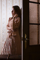 Young woman stands in shadow of doorway in Russian apartment