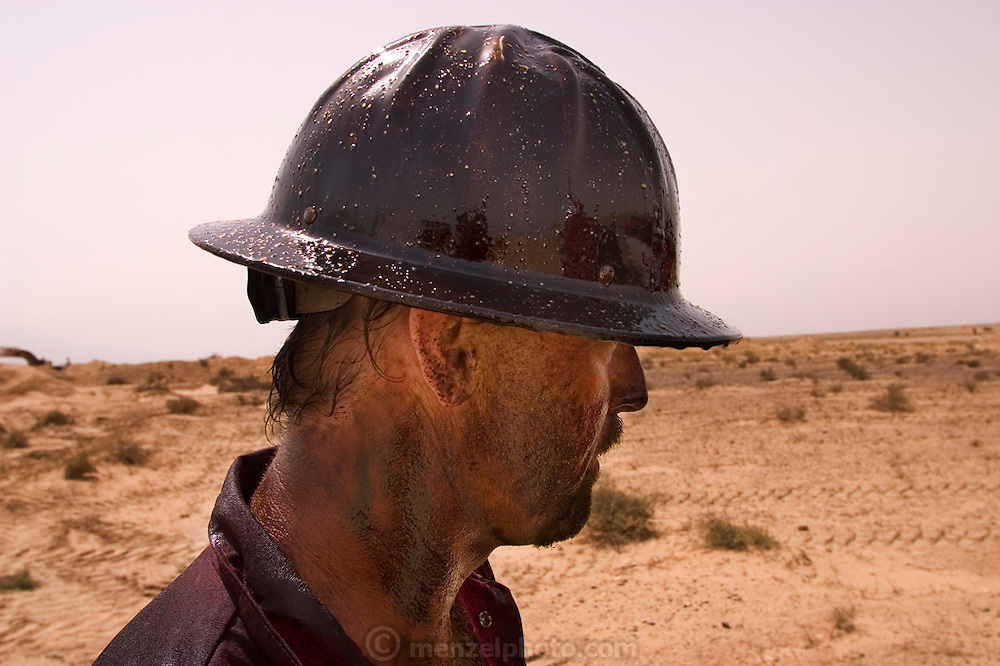 """Mike of Boots and Coots after getting covered with oil while running a backhoe. The gusher was capped two hours later using a """"stinger,"""" a tapered pipe on the end of a long steel boom controlled by a bulldozer. Drilling mud, under high pressure, is pumped through the stinger into the well, stopping the flow of oil and gas. The Rumaila field is one of Iraq's biggest oil fields with five billion barrels in reserve. Rumaila is also spelled Rumeilah."""