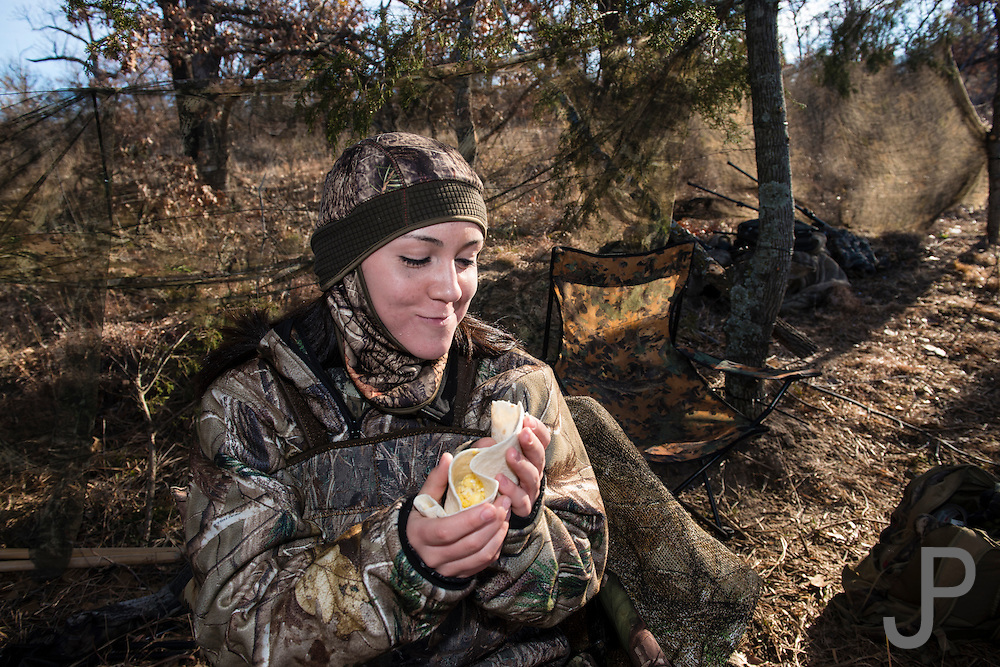 Ceara Prather from Dewey, Oklahoma eats a homemade breakfast burrito while duck hunting with her dad in Shamrock, Oklahoma