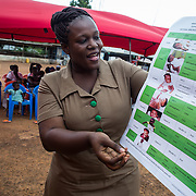 Adelaide Serwaa Simpeh, a community health nurse, gives a health talk about vaccinations to moms gathered at a vaccine clinic in a bus station near Larteh, Ghana, in the Akwaupem North District. <br /> <br /> The GAVI Alliance helps to buy many of the vaccines in Ghana and supports Ghana's government health service and local partners with training and improvement of refrigerated storage for the medicines. <br /> <br /> Ghana now has one of the best-performing immunization programs in the developing world, and is is increasingly a model for its neighbors. In 2012, Ghana became the first GAVI-supported country in Africa to simultaneously introduce vaccines against pneumococcal disease and rotavirus, which tackle the world's leading killers of children -- pneumonia and diarrhea.