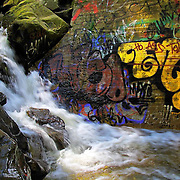 creek and waterfall in niles canyon with grafitti and old mattress.