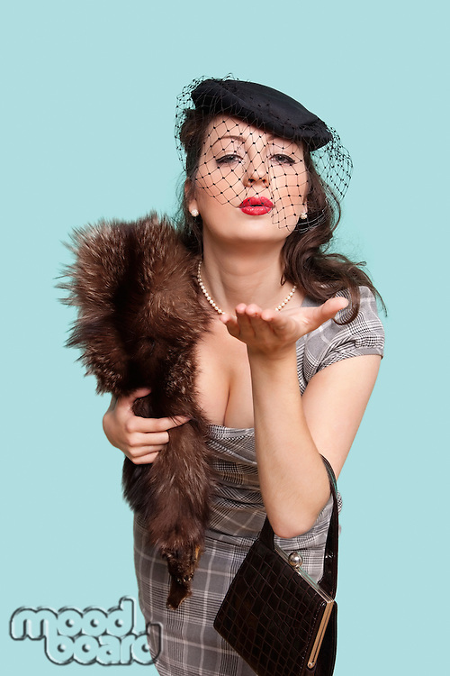 Portrait of beautiful young woman with fur boa blowing kisses against blue background