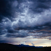 Andrew Whiteford riding Teton Singletrack as a summer thunderstorm highlights sunset.