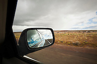 View in the side mirror of a car while driving on a highway in Eastern Oregon.