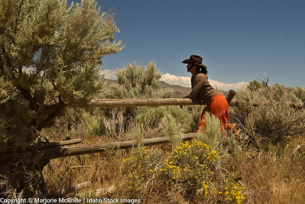 Cowgirl wearing a skirt leans on a wood fence surrounded by flowering sage brush.   Blaine County, near Sun Valley, Idaho.    Model Release