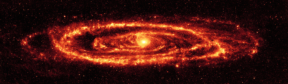 NASA's Spitzer Space Telescope infrared view of the famous galaxy Messier 31, also known as Andromeda. Spitzer's 24-micron mosaic (main image) is the sharpest image ever taken of the dust in a spiral galaxy, other than our Milky Way. Asymmetrical features are seen in the prominent ring of star formation, which appears to be split into two pieces, forming the hole to the lower right. These features may have been caused by interactions with satellite galaxies around Andromeda as they plunged through its disk. At optical wavelengths, the centre of the galaxy is dominated by a large bulge. This bulge is far less pronounced in the Spitzer 24-micron infrared image, allowing us to see the delicate tracings of spiral arms in the inner region that reach into the centre of the galaxy.