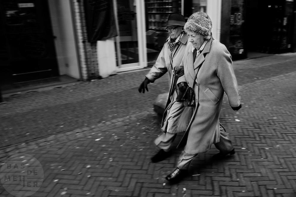 Twee oudere vrouwen lopen gearmd door het centrum van Utrecht