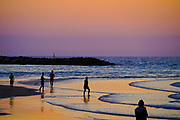 Silhouette of people on the beach at sunset. Photographed on the Tel Aviv Beach, Israel in March