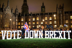 © Licensed to London News Pictures. 10/12/2018. London, UK. Anti-Brexit campaigners stand with illuminated letter spelling out 'VOTE DOWN BREXIT' outside Parliament after Prime Minister Theresa May announced that the vote on her proposed withdrawal deal will be postponed. Photo credit: Rob Pinney/LNP