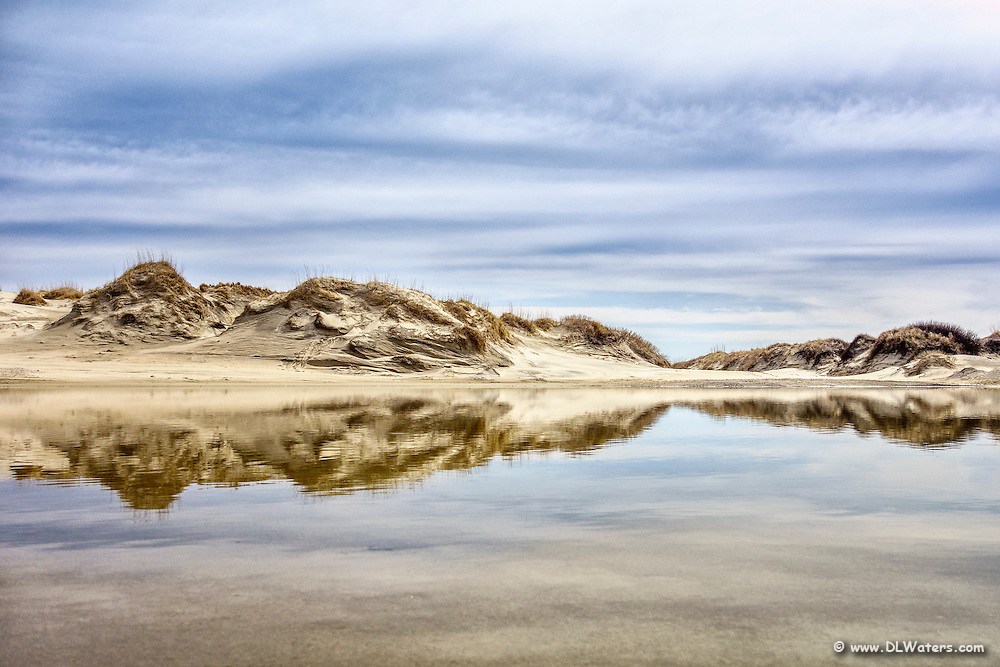 Reflection of sand dunes in still water at Oregon Inlet on the Outer Banks.