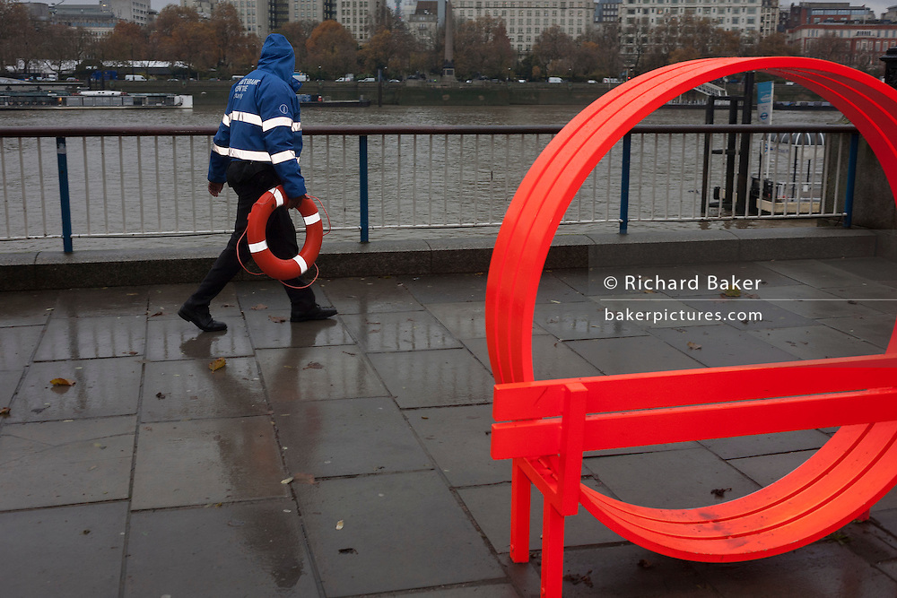 An employee of London's Southbank carries a life ring near pavement artwork.