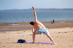 Portobello, Edinburgh. Scotland, UK. 12 April, 2020. Easter Sunday afternoon in sunny weather the public are outdoors exercising and walking on Portobello beach. The popular beach and promenade was very quiet and people were mostly exercising proper social distancing. Pictured; Man practicing yoga on Portobello beach. Iain Masterton/Alamy Live News