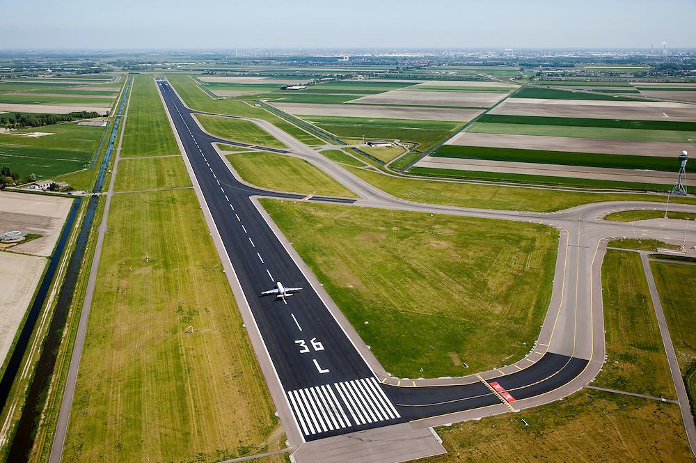 Nederland, Noord-Holland, Haarlemmermeer, 12-05-2009. Nederland, Noord-Holland, Haarlemmermeer, 12-05-2009; Polderbaan of ook Vijfde baan Schiphol gezien vanuit het zuiden met vertrekkende vliegtuig, autoweg A9 en Spaarnwoude aan de horizon. Schiphol heeft drie verschillende banen die paralel liggen, de markering 36 L laat piloten weten dat het gaat om de Linkerbaan in Noordelijke richting (360 graden), bij een nadering vanuit het noorden heet de Polderbaan de 18L, 180 graden, left. Vanuit het zuiden gezien ligt naast de Polderbaan in het midden de Zwanenburgbaan (36C - centre) en daar weer naast de meest rechtste baan, de Kaagbaan (36R). Het banengebruik is afhankelijk van de windrichting, geluidsbelasting van de omgeving en dergelijk.  Een vliegtuig begint net aan zijn vlucht. Air view on an airoplane, about to take off from a runway (the so called Polder runway) of Schiphol Airport, The Netherlands.  Swart collectie, luchtfoto (toeslag); Swart Collection, aerial photo (additional fee required).foto Siebe Swart / photo Siebe Swart