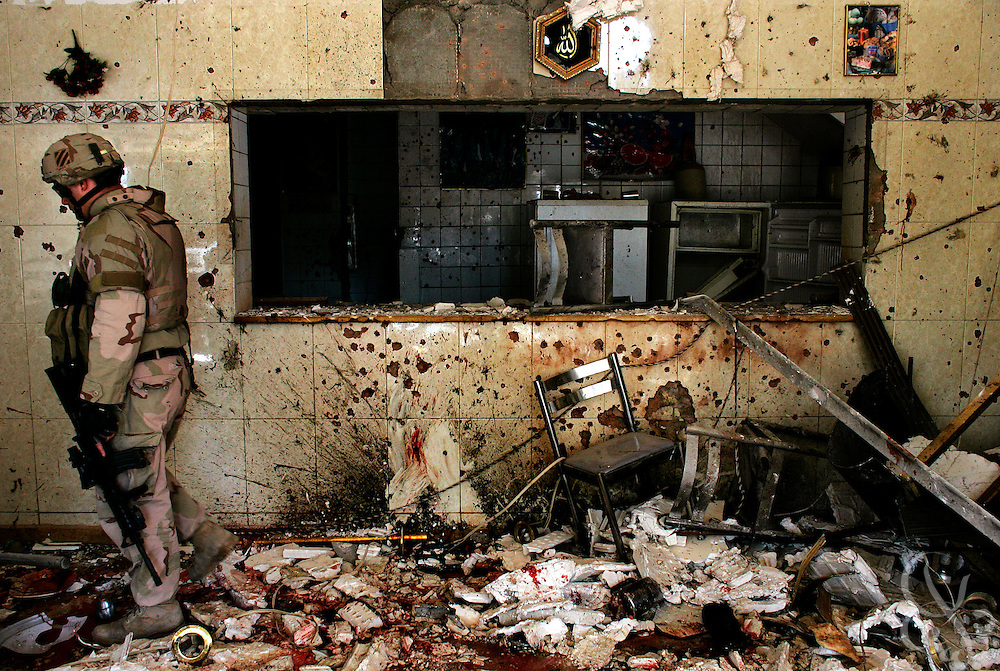 """A solider from the U.S. Army Third Infantry Division's 1st Battalion 9th Field artillery regiment investigates the scene of a suicide bombing that killed at least 33 people and wounded more than 17, at the Baghdad restaurant """"Qaduri"""" November 10, 2005. Qaduri was a popular breakfast spot in Baghdad, frequently packed each morning with working class Iraqis and Iraqi police, who appeared to be the target."""