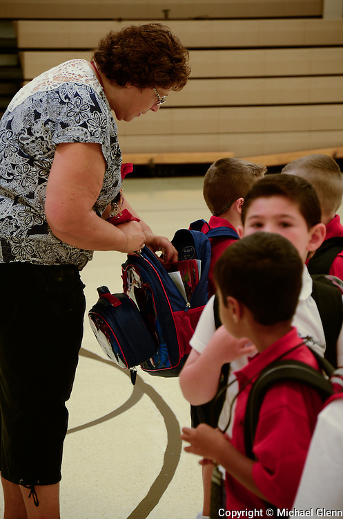 Jackson NJ, USA 04Sept2013 First day of school for students at Saint Aloysius Kindergarten teacher Mrs Stedman helps a student with his backpack