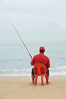 Man in red tshirt fishing from red plastic chair Cape Town South Africa