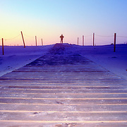 Man standing on a wooden boardwalk through the dunes at sunrise. Cape Hatteras, North Carolina