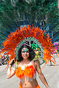 A marcher wears an orange costume and an elaborate fan with peacock feathers.
