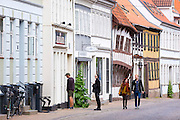 Tourists, shops and medieval buildings in street scene in the old town in Odense on Funen Island, Denmark